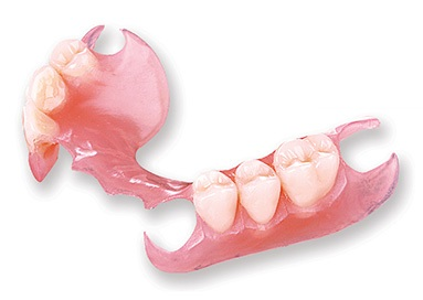 photograph of a removable partial denture replacing three back teeth on each side of the mouth, made entirely of plastic